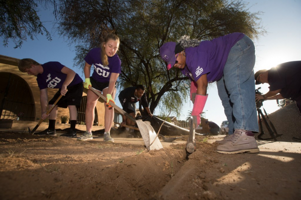Alumni shoveling at a volunteer event